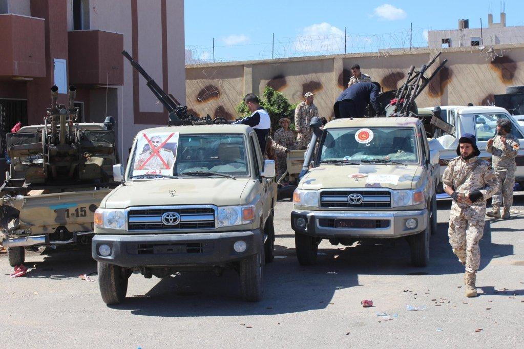 ANSA / مسلحون يتوجهون على مركبات تحمل صورا مشوهة لقائد الجيش الوطني خليفة حفتر، قبل التوجه إلى مناطق القتال للدفاع عن طرابلس. المصدر: إي بي إيه.