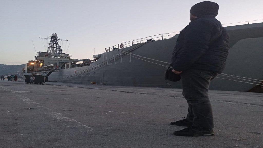 محمود* أمام السفينة العسكرية اليونانية في ليسبوس.