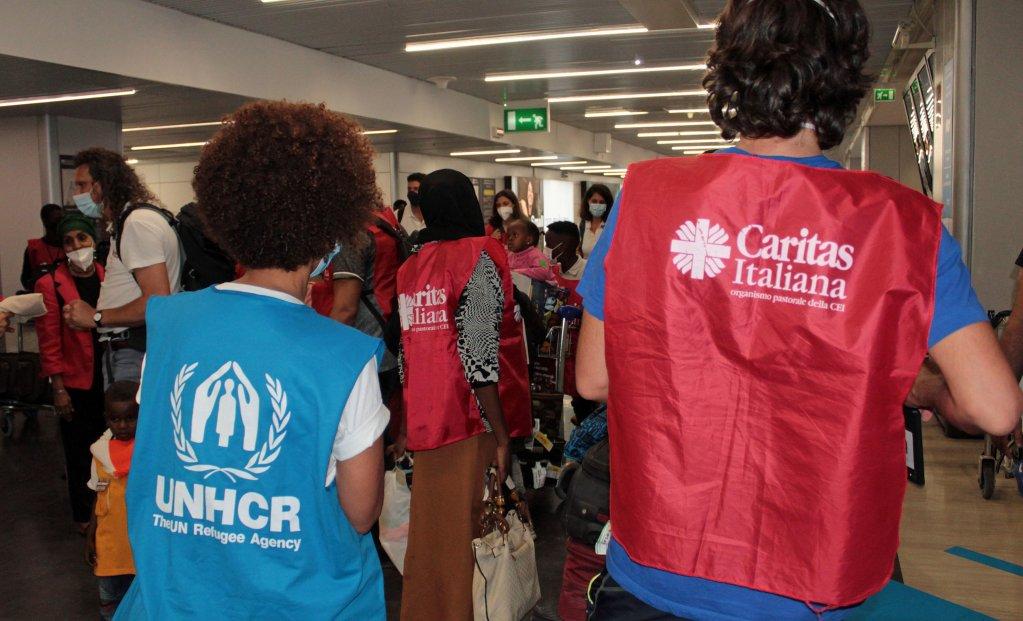 موظفو مفوضية اللاجئين ومؤسسة كاريتاس يقدمون المساعدة للاجئين الوافدين عبر الممرات الإنسانية في مطار فيوميتشينو الإيطالي. المصدر: أنسا.