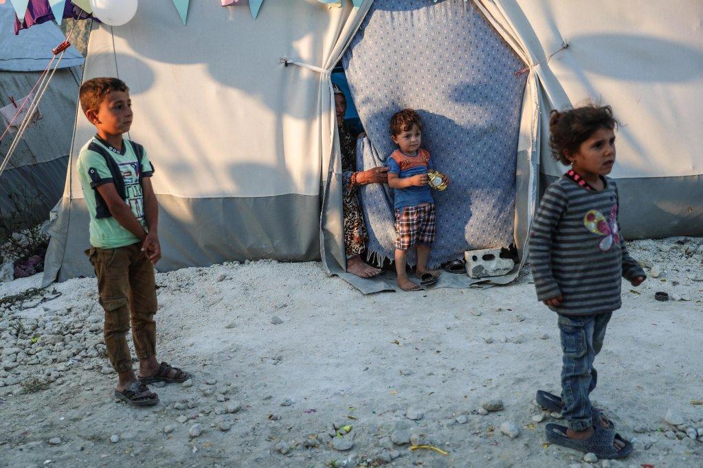 أطفال سوريون يقفون داخل مخيم للنازحين في خربة الجوز بمحافظة اللاذقية السورية. المصدر: إي بي إيه/ محمد بدر.
