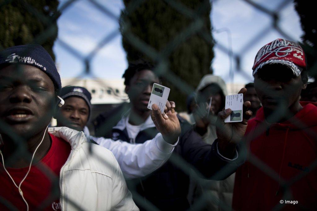 Des migrants expulsés du centre Castelnuovo di Porto, près de Rome, montrent leur permis de séjour. Crédit : Imago/Christian Minelli