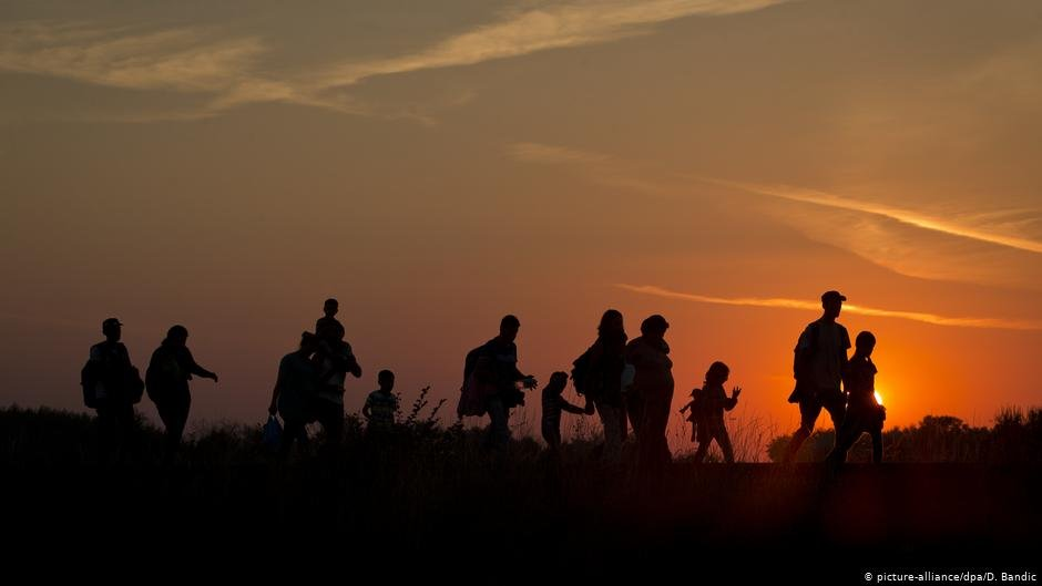 Refugees walking through a field | Photo: Picture-alliance/dpa/D.Bandic