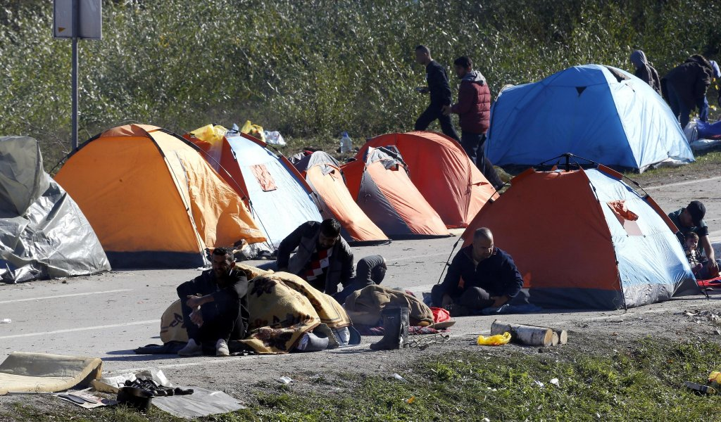 A group of migrants attempting to cross into Croatia gather around tents erected near the Maljevac border crossing, Bosnia and Herzegovina, 25 October 2018. EPA/FEHIM DEMIR