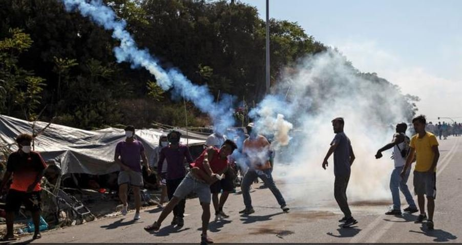 Refugees and migrants from the destroyed camp of Moria throw back tear gas fired by riot police during clashes, on the island of Lesbos, Greece, September 12, 2020 | Photo: REUTERS/Alkis Konstantinidis