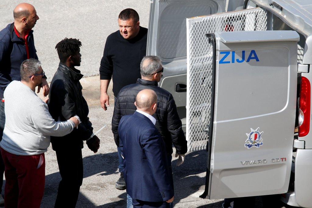 Suite au détournement d'un pétrolier, cinq migrants ont été menottés et emmenés dans un fourgon de police. Crédit : Reuters