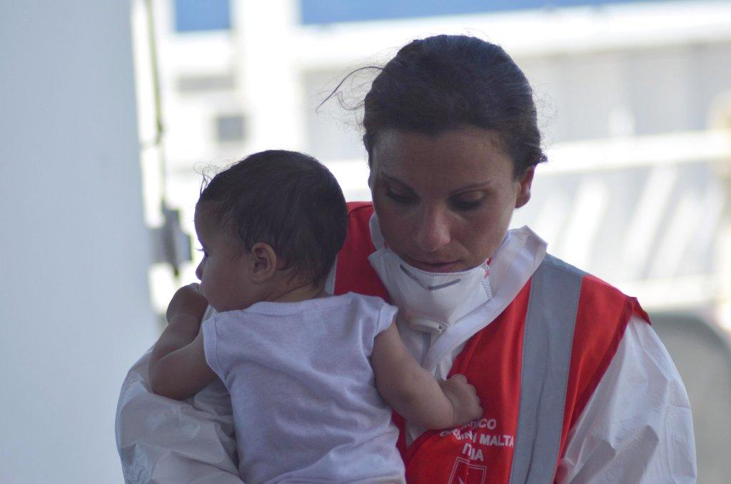 ANSA / طبيبة تحمل أحد أطفال المهاجرين. المصدر: أنسا / المكتب الصحفي لفرسان مالطا.