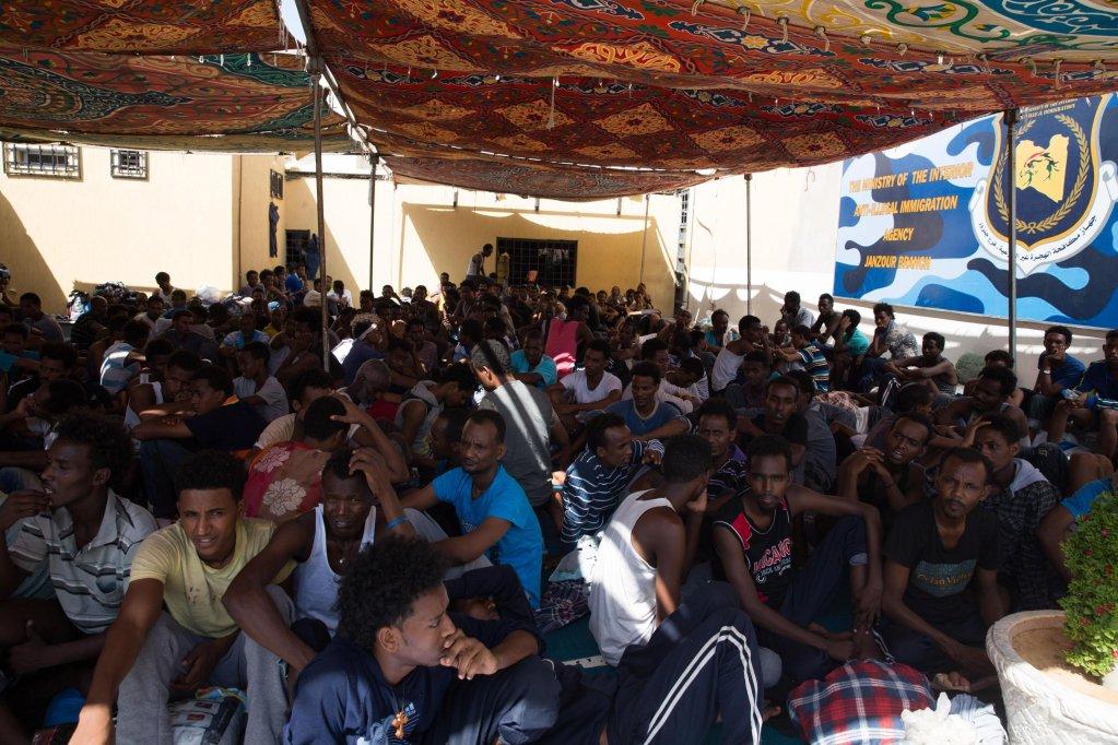 مهاجرون يجلسون في مركز احتجاز نجيلة في طرابلس، بعد فرارهم من أحد المراكز بالقرب من المطار، بسبب الاشتباكات في محيطه. المصدر: إي بي أيه.