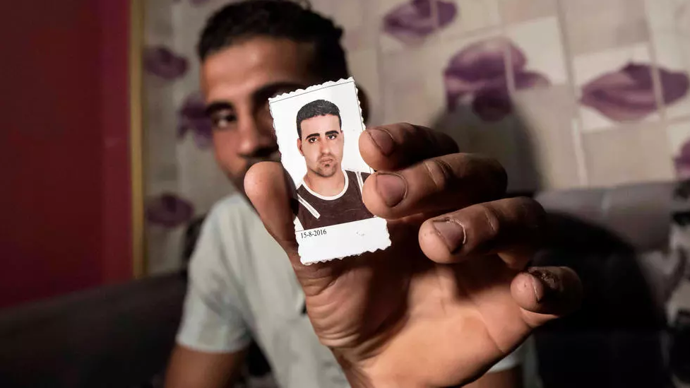 Egyptian Karim Farrag displays a picture of his brother Mohamed who went missing in Libya while trying to get to Europe | Photo: Khaled DESOUKI AFP