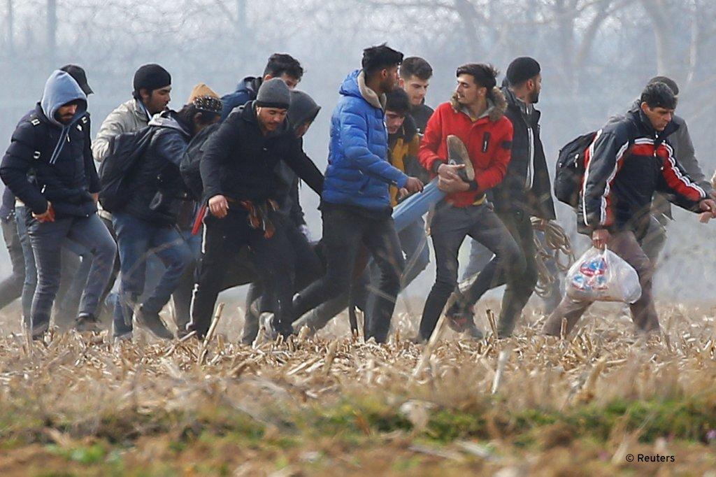 مهاجرون يحملون مصاباً بالقرب من معبر بازاركولي التركي. المصدر: رويترز