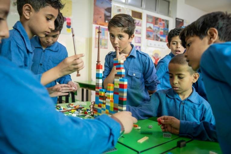 Refugee boys playing with Lego | Photo: UNICEF/UN0250052/Herwig