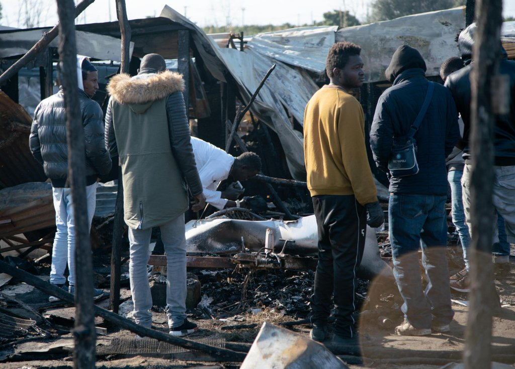 ANSA / مجموعة من عمال الزراعة المهاجرين يتحلقون حول بقايا مسكن شاب فقد حياته إثر حريق في إحدى مدن الصفيح في سان فرديناندو بمنطقة كالابريا جنوب إيطاليا. المصدر: أنسا / ماركو كوستانتينو.