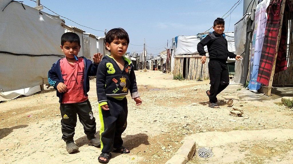 أطفال سوريون أمام خيمهم في أحد المخيمات بمنطقة عكار شمال لبنان، 6 نيسان\أبريل 2021. رويترز