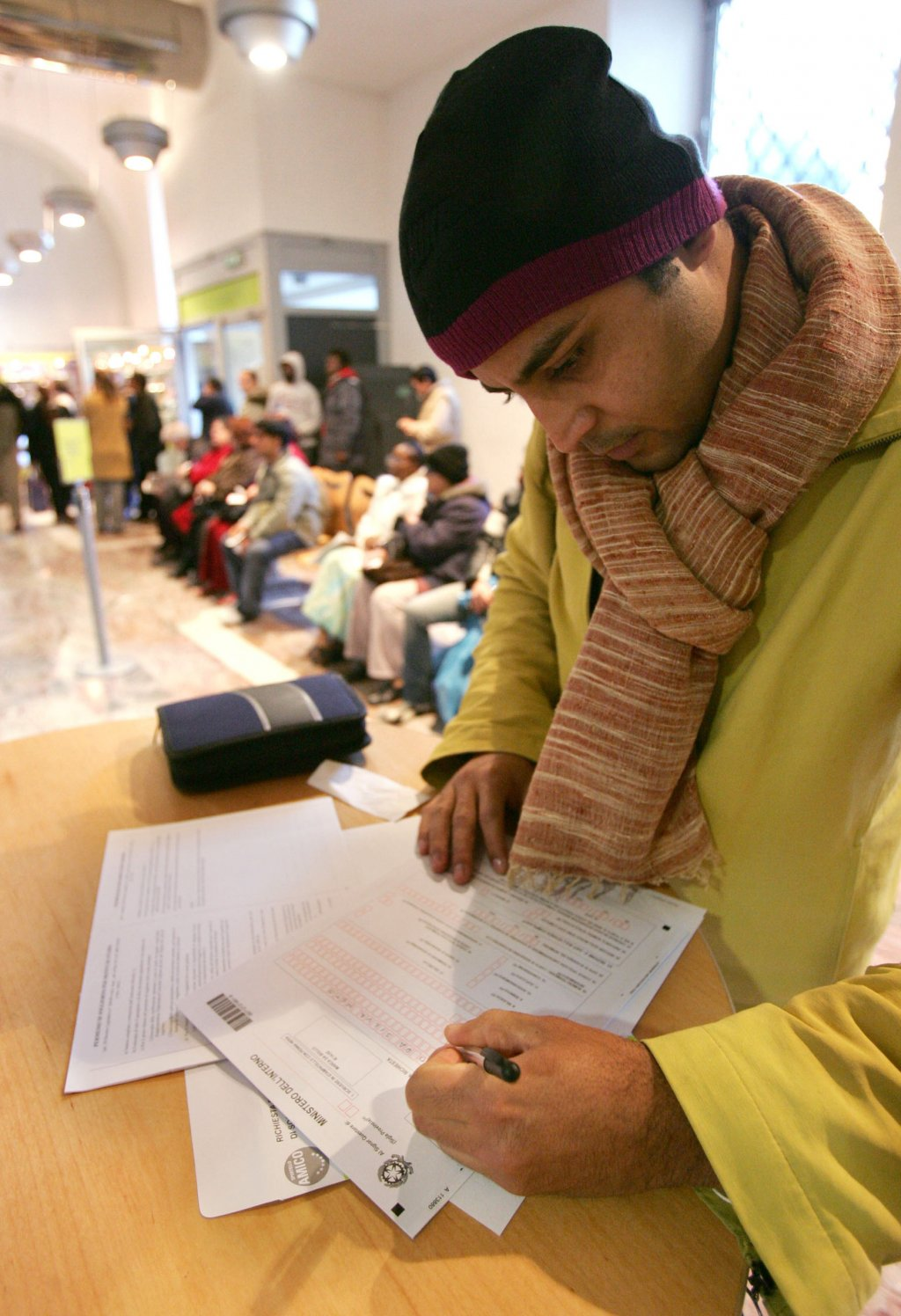 Foreign citizens filing stay permit requests at a Rome post office   Photo: ARCHIVE/ANSA/ALESSANDRO DI MEO