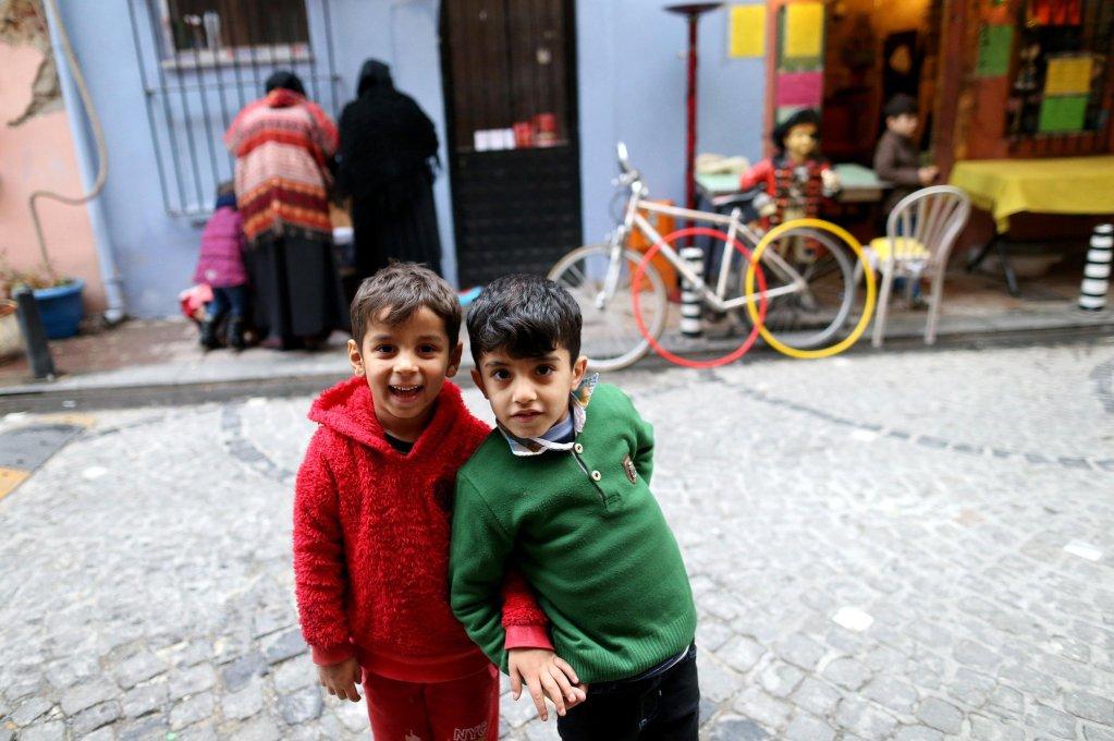 ansa / أطفال سوريون لاجئون ينتظرون أثناء قيام أمهاتهم بفحص ملابس مجانية، في أحد شوارع منطقة بالات التاريخية في أسطنبول. المصدر: إي بي أيه/ إرديم شاهين
