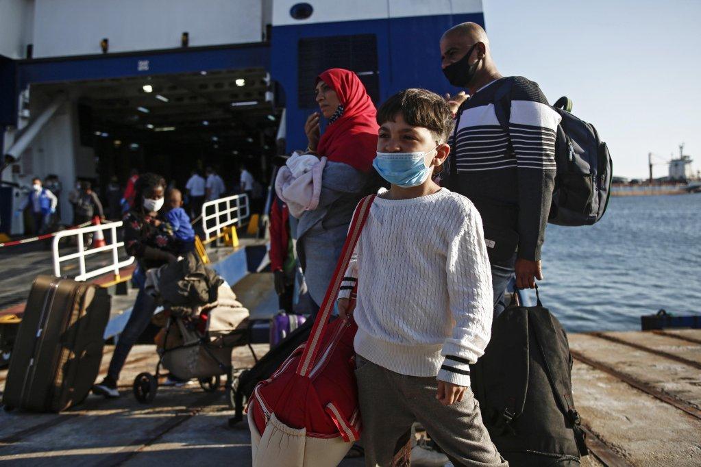 """لاجئون يهبطون من العبارة """"بلوستار كيوس"""" في ميناء لافريو في اليونان في 29 أيلول / سبتمبر 2020، حيث يتم نقل اللاجئين والمهاجرين من ست جزر في شرق بحر إيجه إلى البر الرئيسي. المصدر / إيه بي إي / يانيس كوليسيدس"""