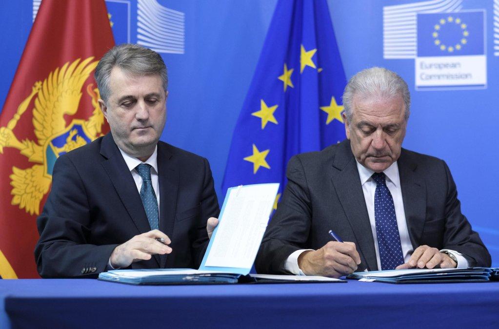 مفوض الاتحاد الأوروبي لشؤون الهجرة، ووزير داخلية الجبل الأسود (إلى يسار الصورة) خلال مراسم توقيع الاتفاقية. المصدر: إي بي أيه/ أوليفر هوسليت.