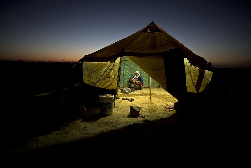 ANSA / لاجئة سورية تميل على ابنتها أثناء قيامها بالطبخ داخل خيمتها في مخيم عشوائي في أطراف مدينة المفرق، الأردن.  المصدر / محمد محيسن.