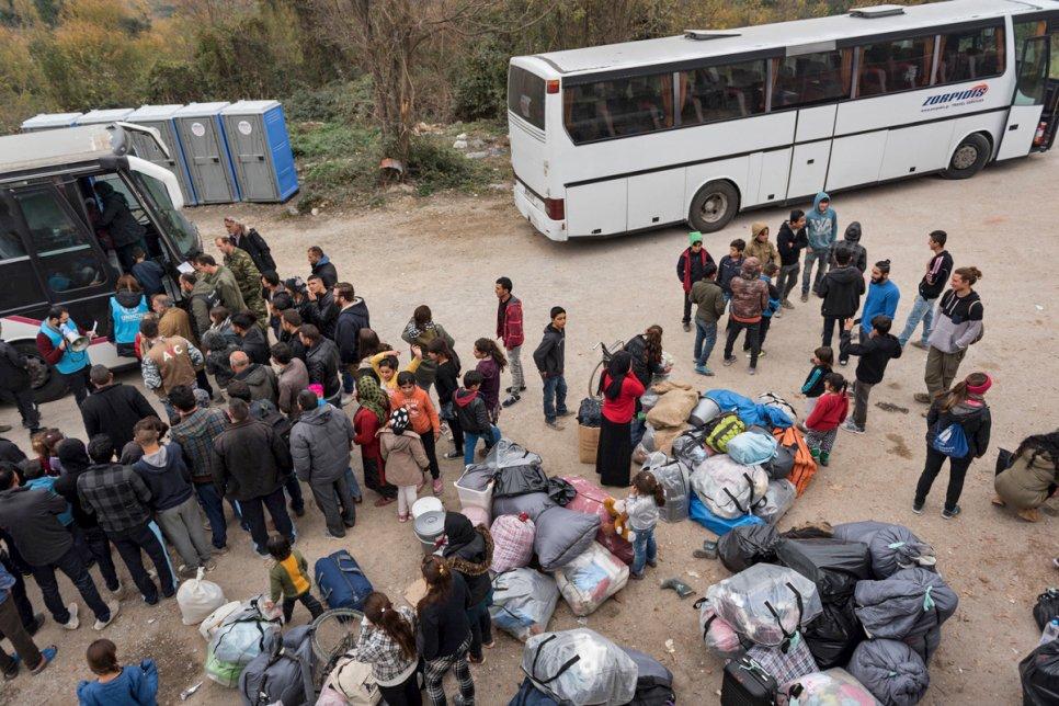 Des familles attendent leur tour pour monter dans un bus qui les transférera depuis des sites de tentes vers des logements en dur. Crédit : HCR / Christos Tolis