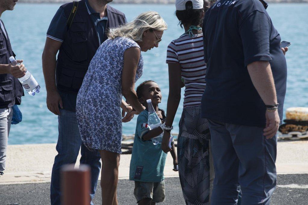 ANSA / طاقم طبي وضباط يساعدون طفلا مهاجرا بعد هبوطه من على متن سفينة حرس السواحل الإيطالية في ميناء بوتزالو في صقلية. المصدر: أنسا/ فرانشيسكو روتا.