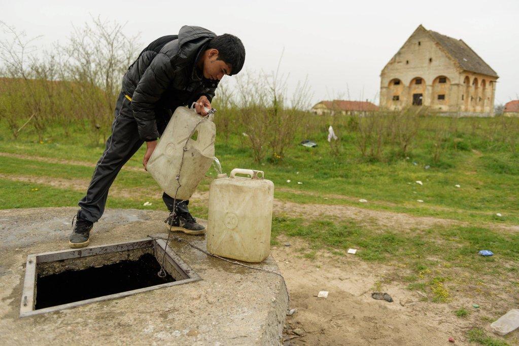 ANSA / قاصر مهاجر يملأ وعاءً بلاستيكياً بالمياه من بئر قبالة أحد الأبنية المهجورة في ضواحي هورجوس في شمال صربيا، بالقرب من الحدود المجرية. المصدر: إي بي إيه/ إدفارد مولنار.