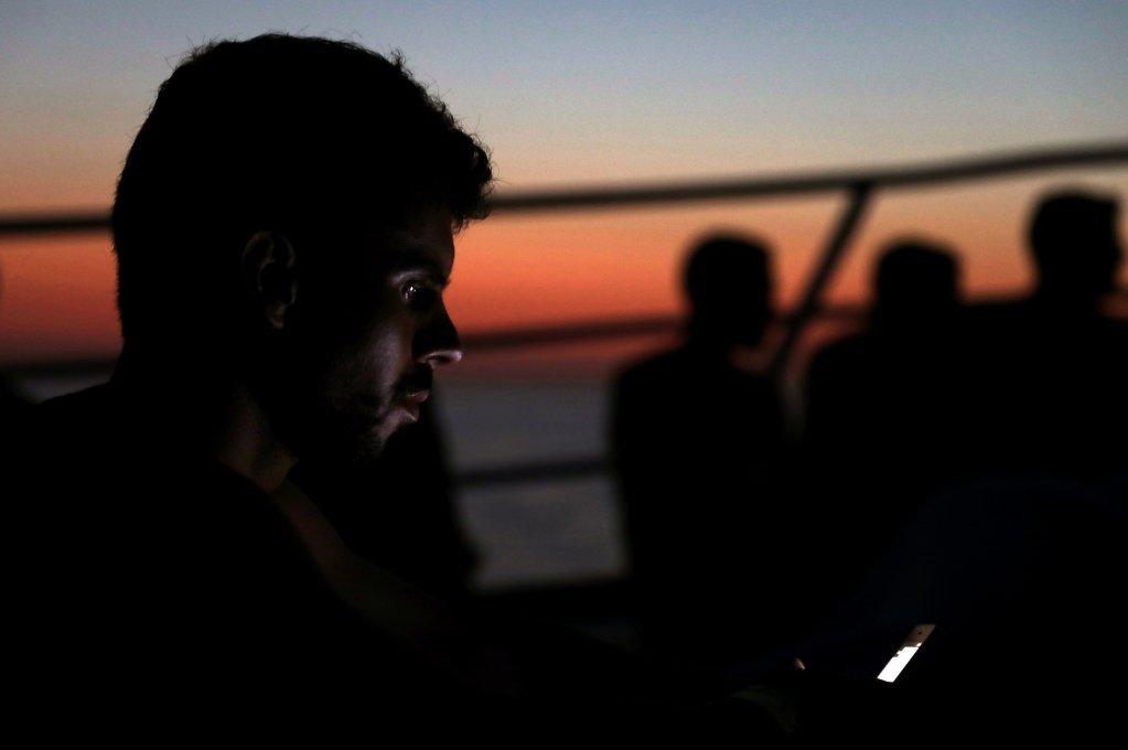 صورة من الأرشيف لمهاجر يحاول الاتصال بعائلته على متن قارب أوبن آرمز. المصدر: رويترز