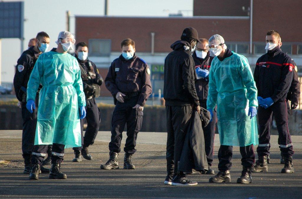 BERNARD BARRON / AFP |Des gendarmes et des pompiers autour d'un migrant dans le port de Calais, le 7 avril 2020.