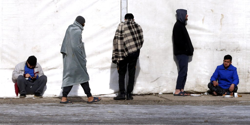 مهاجرون يستريحون في العراء في الثكنات العسكرية السابقة في بلازوي إحدى ضواحي سراييفو. المصدر: إي بي إيه / فهيم دمير.