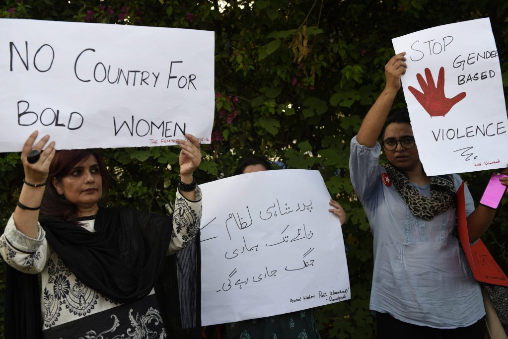 People hold placards during a protest against honor killings in Islamabad, Pakistan | Photo: EPA/T. Mughal