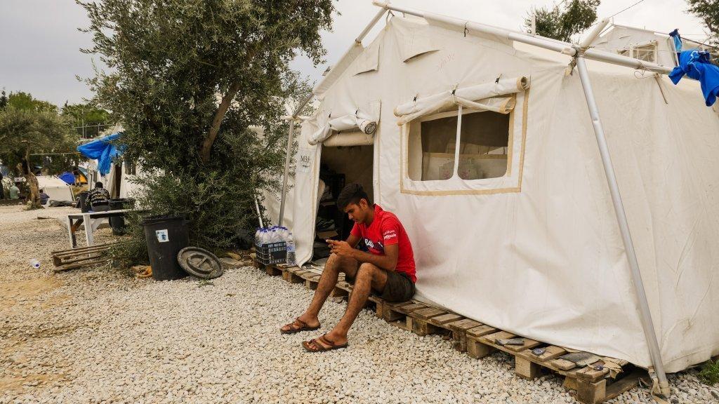 يو مهاجر چي په ليسبوس ټاپو کي د خېمې دباندي ناست دی / انځور: عاصم سليم