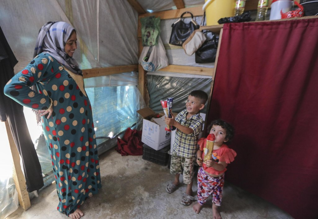 Khadija Ismail Al-Jneid, a 32-year-old Syrian refugee woman from Al-Raqqa, Syria, and her children stand inside her makeshift shelter at Al-Basma Syrian refugee camp in Deir Zanoun area in the Bekaa valley, eastern Lebanon, 19 June 2018. EPA/Nabil Mounzer