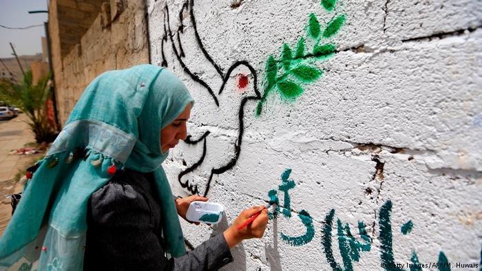 فنانة يمنية ترسم على الحائط رمزاً لما يريده جميع اليمنيين، وهو السلام