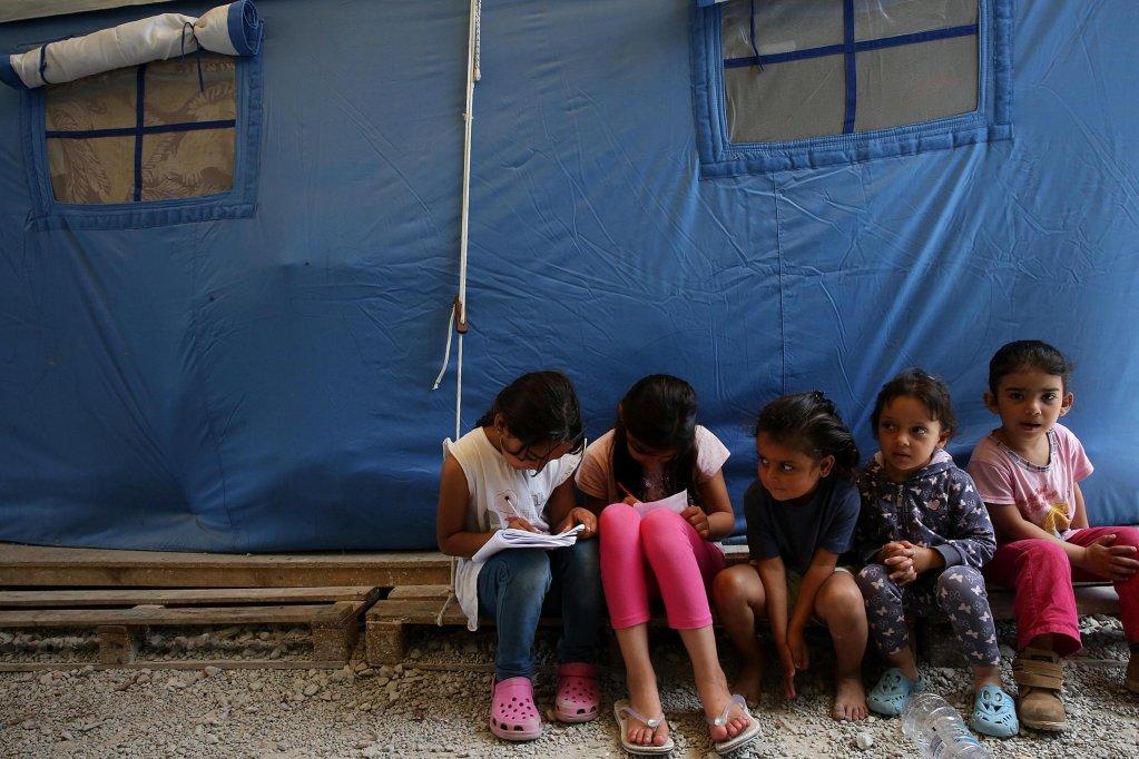 """أطفال لاجئون يجلسون في أحد الأقسام المخصصة للعائلات في مركز تحديد الهوية في مخيم موريا بجزير ليسبوس. المصدر: """"إي بي إيه""""/ أوريستيس بانايوتو."""