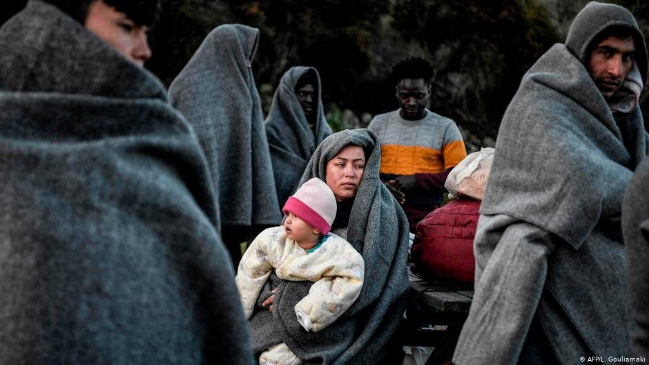 People warpped in thick grey blankets stand while a woman in a blanket rests with a baby on her knee | Photo: AFP/L.Gouliamaki