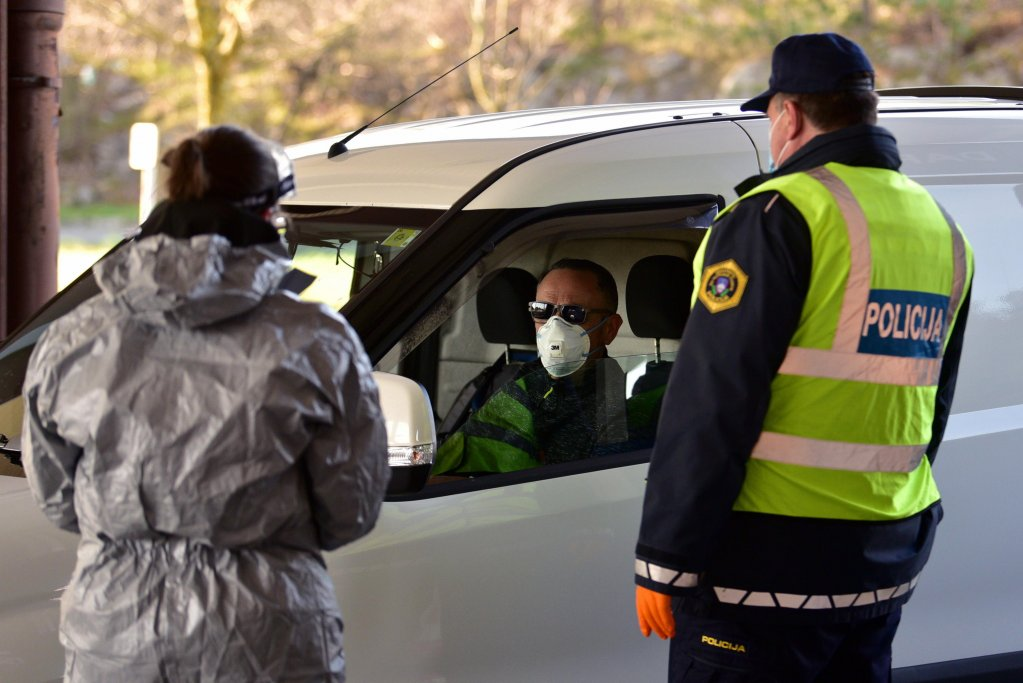 Slovenian police and health workers approach a driver for questioning at the Slovenian-Italian border crossing of Fernetici, Slovenia | Photo: EPA/Igor Kupljenik