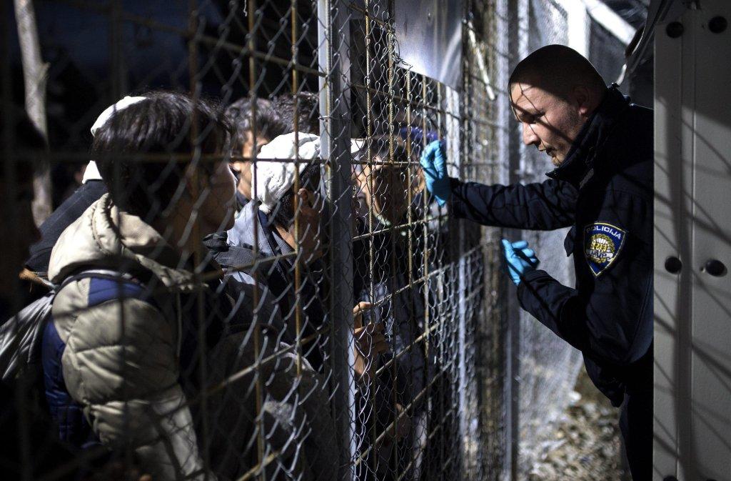 """ansa / شرطي يتحدث للاجئين سوريين وعراقيين أثناء انتظارهم عبور الحدود اليونانية المقدونية لمواصلة رحلتهم عبر مقدونيا وصربيا وكرواتيا وسلوفينيا إلى النمسا، ومنها لألمانيا باعتبارها الهدف النهائي. المصدر: """"إي بي إي""""/ جورجي ليكوفيسكي"""
