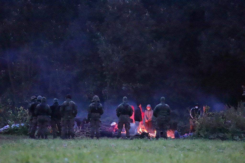 عناصر من حرس الحدود البولندي يراقبون مجموعة من المهاجرين أقاموا مخيما عشوائيا بالقرب من قرية أوسنارز جورني المحاذية للحدود مع بيلاروسيا، 18 آب/أغسطس 2021. رويترز