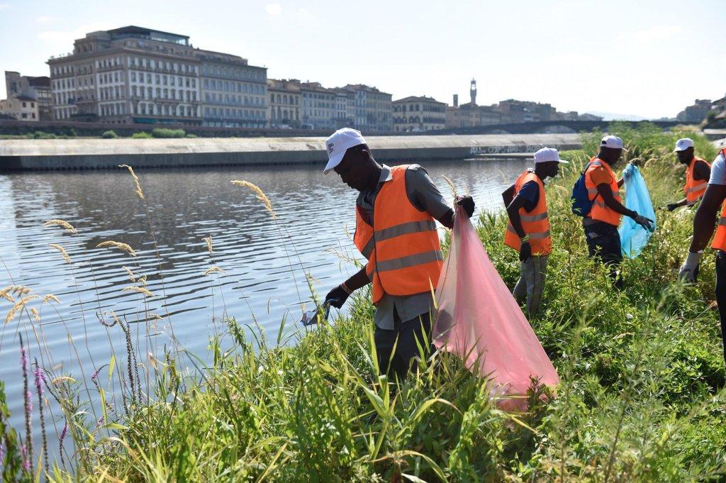 مهاجرون ينظفون شواطئ النهر في فلورنسا. المصدر: أنسا/ ماوريزيو ديل انوسنيتى.