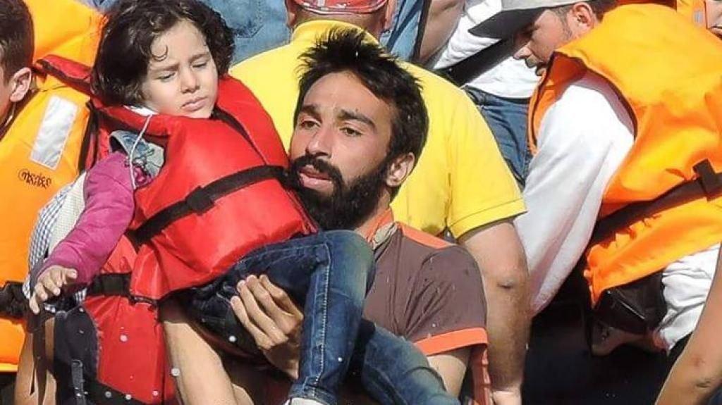 Kinan Kadoni porte une enfant hors de l'embarcation, île de Lesbos, Grèce. Crédit : Rutget Verhaegen