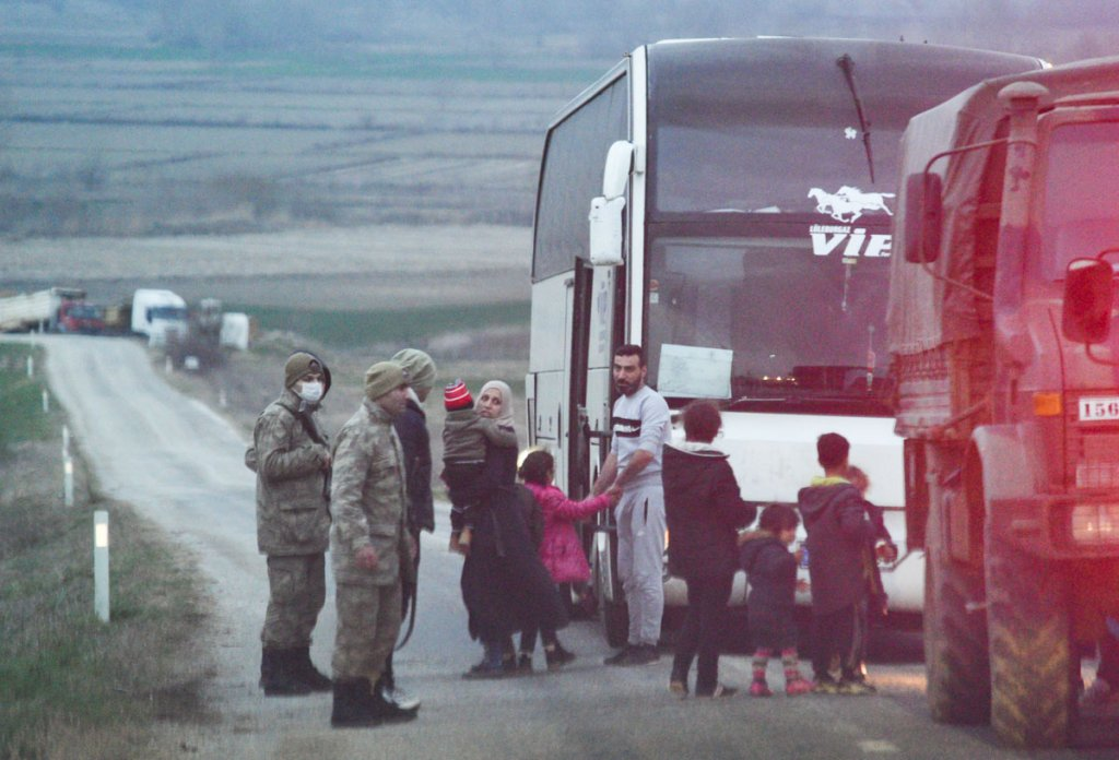 Turkish military transfers migrants to a bus to bring them to a transit center in d'Uzunköprü. The migrants were pushed back by Greek border police | Photo: Mehdi Chebil