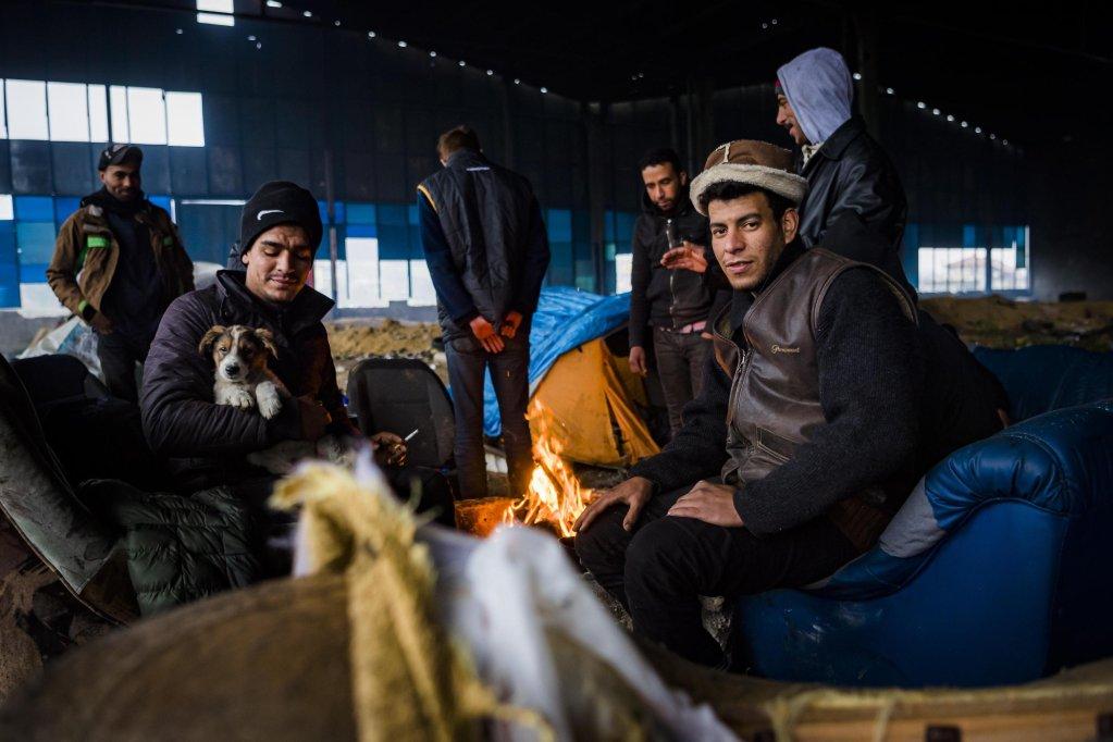ANSA / مهاجرون يتدفؤون قرب موقدة نار في مخيم غير شرعي داخل مصنع مهجور في فيلكا كلادوشا بالقرب من مدينة بيهاتش البوسنية. المصدر: إي بي إيه / جان كريستوف بوت.