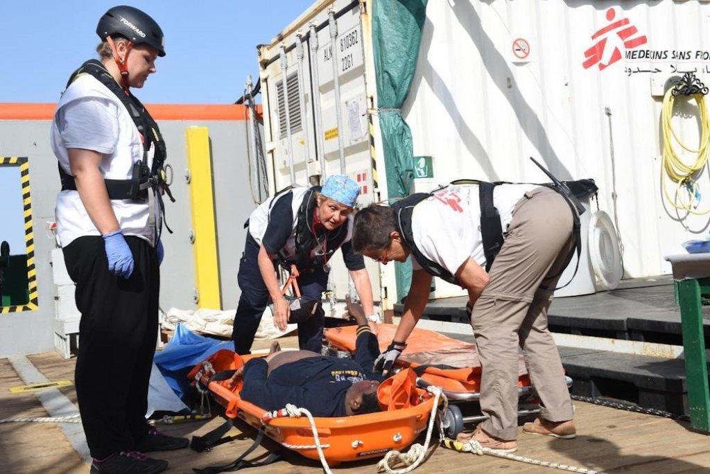 """بعض ناشطي منظمة """"أطباء بلا حدود"""" يساعدون مهاجراً على النزول من قارب في باليرمو. المصدر: أنسا / منظمة أطباء بلا حدود."""