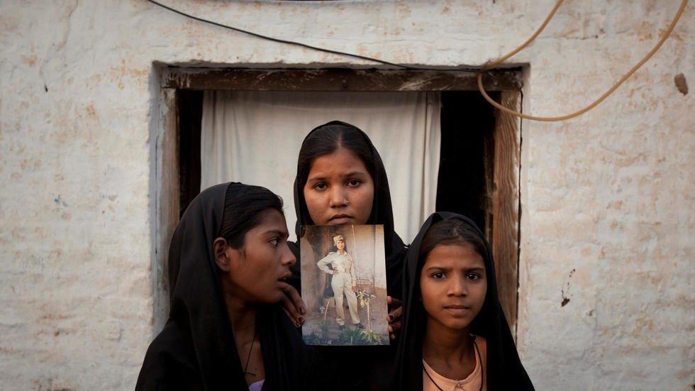 در سال ٢٠١٠ دختران آسیه بیبی تصویری از مادر شان را در دست گرفتهاند.  عکس از ادریس لطیف/ رویترز