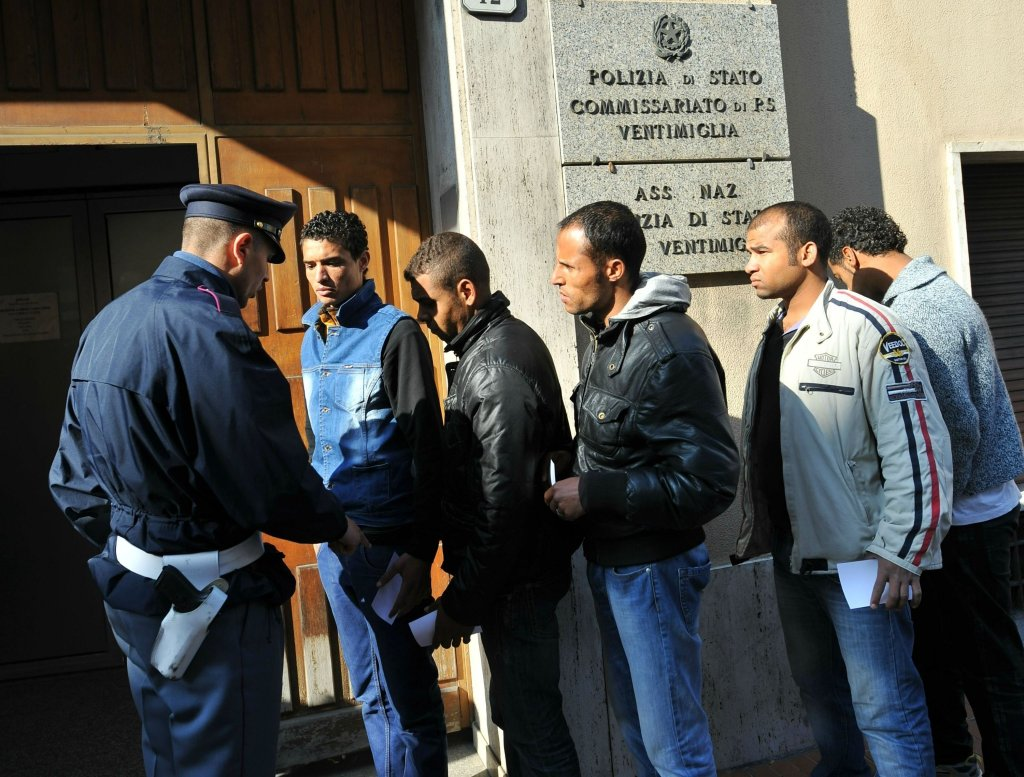Immigrants in line for the requesting of stay permits at a police station in Ventimiglia, Italy  Photo: ANSA / LUCA ZENNARO