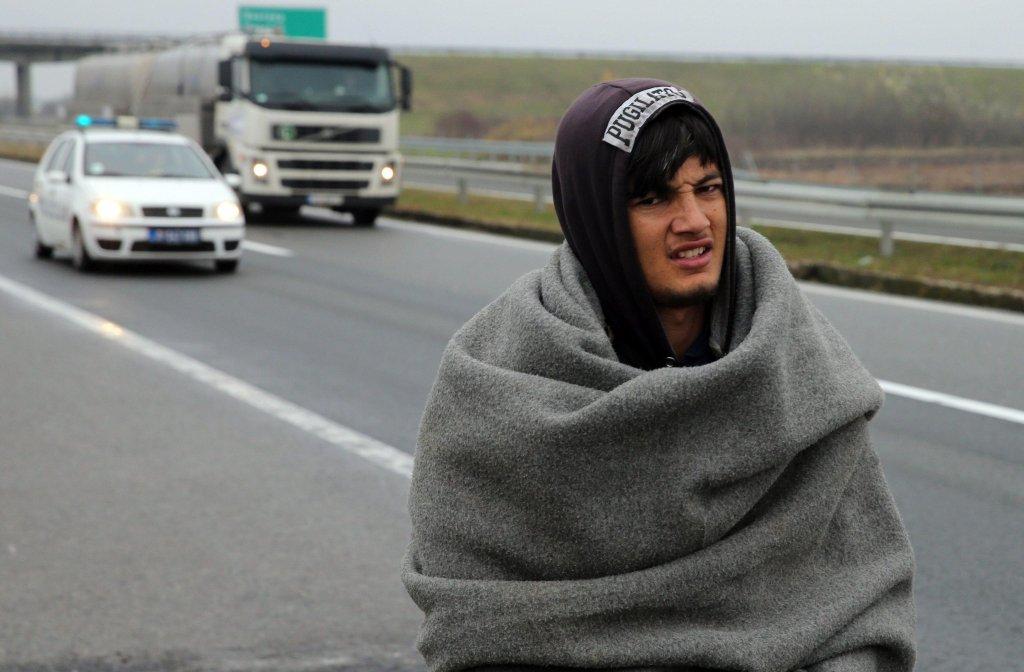 ANSA / مهاجر يسير تحت رقابة سيارة الشرطة على الطريق الرئيس بين بلغراد وزغرب. المصدر: إي بي إيه/ كوتشا سوليمافوفيتش.