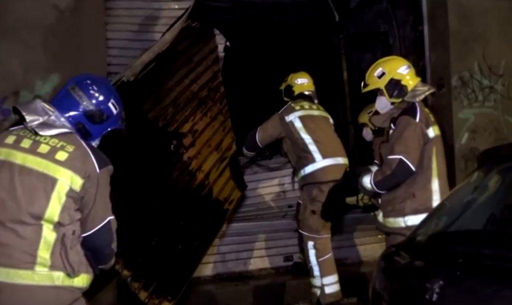 جهود إطفاء الحريق الذي اندلع في المبنى الذي يقطنه المهاجرون على مشارف برشلونة. رويترز