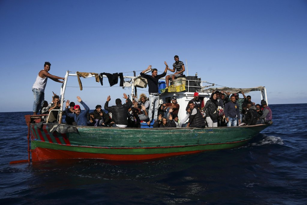 A boat carrying 48 migrants from Tunisia near the Portuguese Navy Oceanic Patrol Vessel 'Viana do Castelo' off the coast of Pozzallo, Sicily, Italy | Photo: EPA/JOSE SENA GOULAO