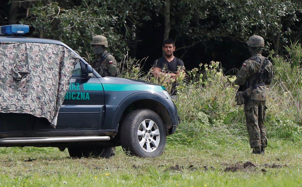 Un migrant bloqué à la frontière entre la Biélorussie et la Pologne se tient près de gardes-frontière polonais, près du village de Usnarz Gorny, le 23 août 2021. Crédit : Reuters