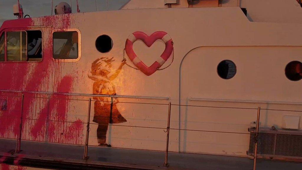 Le bateau est décoré d'un graffiti de l'artiste britannique Banksy représentant une fille portant un gilet de sauvetage et brandissant une bouée en forme de coeur. Crédit : Reuters