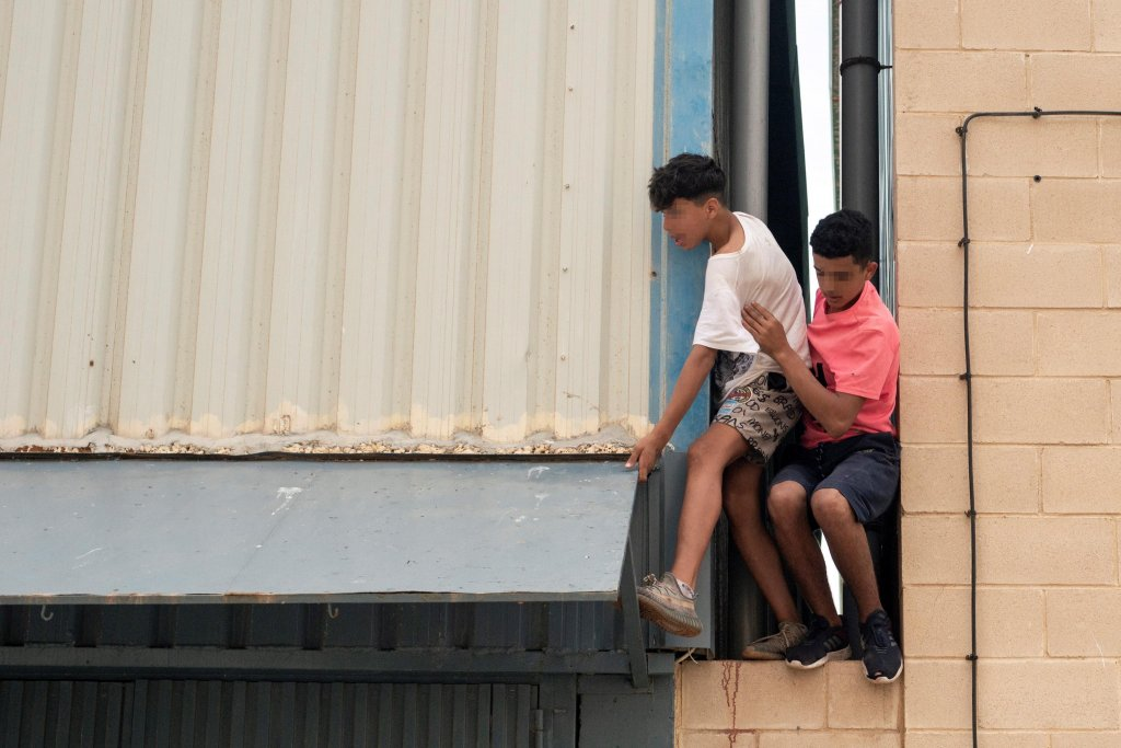 Two underage migrants escaping from an industrial estate next to Tarajal beach, in the city of Ceuta | Photo: ARCHIVE/EPA/BRAIS LORENZO