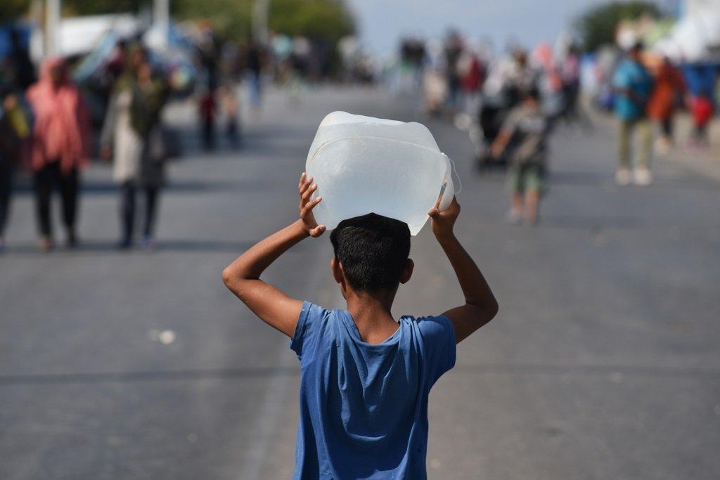 طفل يحمل عبوة مياه متوجها إلى مكان إقامة عائلته على الطريق الواصل بين مخيم موريا ومدينة ميتيليني. الصورة: مهدي شبيل